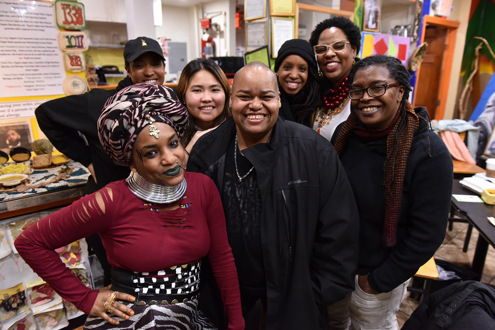 Boston artists (left to right) Nahdra Ra, Kendra Hicks, Ngoc-Tran Vu, Melissa Alexis, Latifa Ziyad and Letta Neely meet with Toshi Reagon (center) at Dorchester's Oasis Vegan Veggie Parlor to discuss the Parable Path Boston. (Photo: Craig Bailey/Perspective Photo)